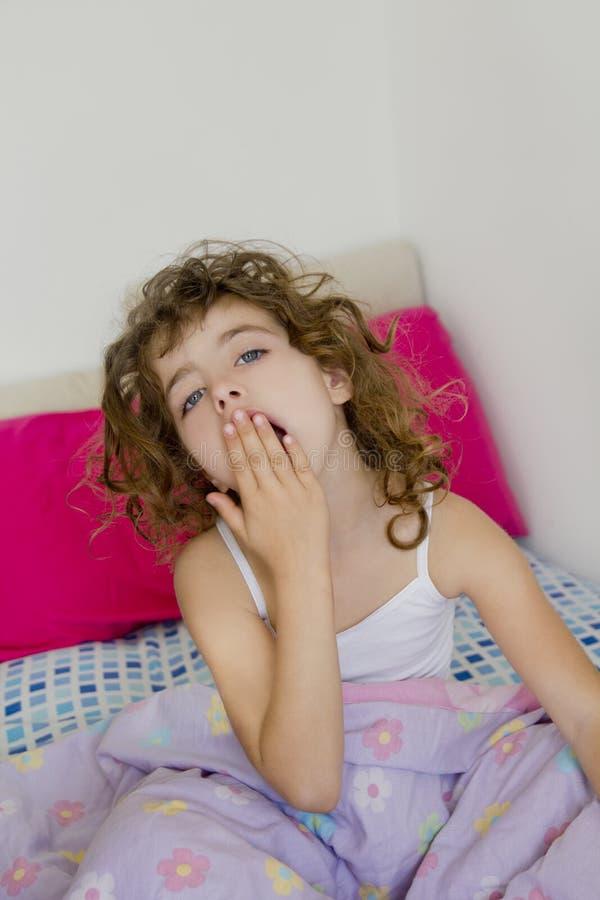 Wecken Morgenhaares des Betts des Mädchens des gähnenden unordentlichen stockfoto