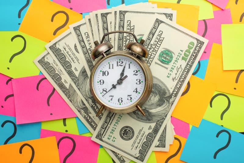 Wecker auf dem Hintergrund von Fragezeichen und US-Dollars, Konzept des Erwerbens des Geldes, Ideen für Gehalt und Zeitverlust a stockfoto