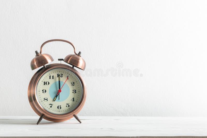 Wecker auf einer weißen Wand und einem hölzernen Regal stockfoto