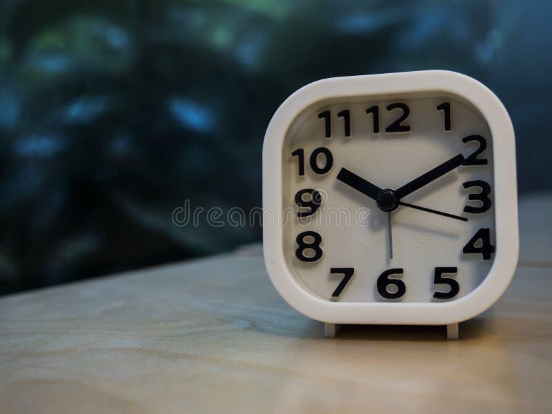 Wecker auf Holztisch mit Unschärfehintergrund im Freien lizenzfreie stockfotos