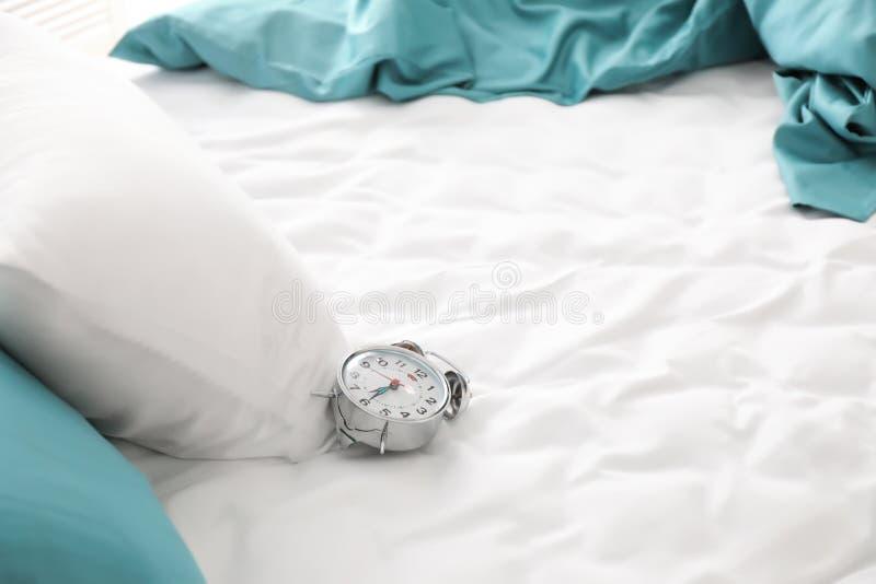 Wecker auf leerem Bett lizenzfreies stockfoto