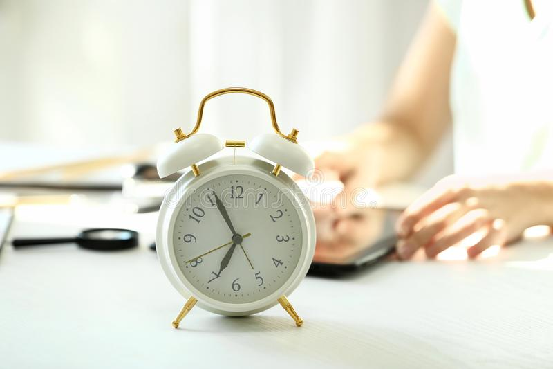 Wecker auf weißer Tabelle im Büro stockfoto