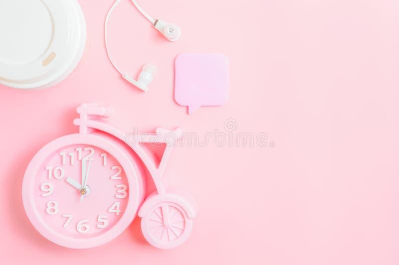 Wecker, ein Glas Kaffee zum Mitnehmen, Kopfhörer und ein notierender Stock auf einem rosa Hintergrund Abstand des gutenmorgens od lizenzfreie stockfotografie