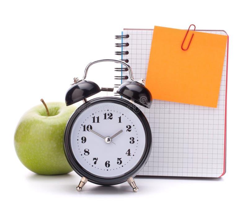 Wecker, leeres Notizbuchblatt und Apfel. stockbild