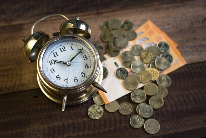 Wecker mit Geld lizenzfreie stockfotografie