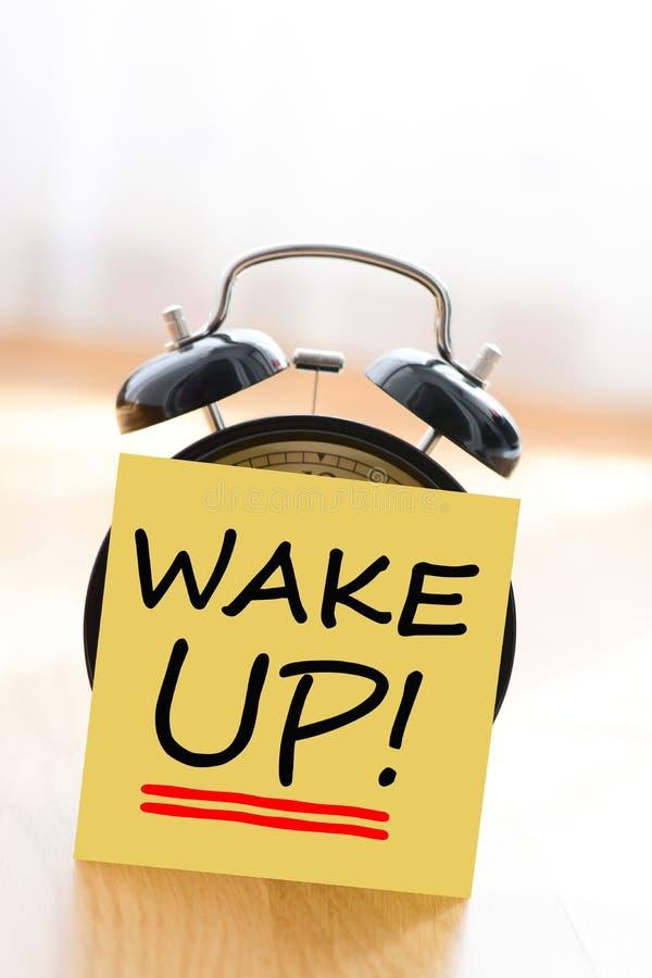 Wecker mit wachen klebende Anmerkung auf lizenzfreies stockbild