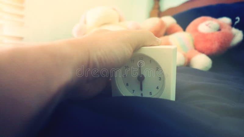 Wecker 6 Uhr morgens auf dem Bett zu Hause Morgenzeit-Hintergrundkonzept, weiche Fokussierung und Weinlesefarbart lizenzfreies stockbild