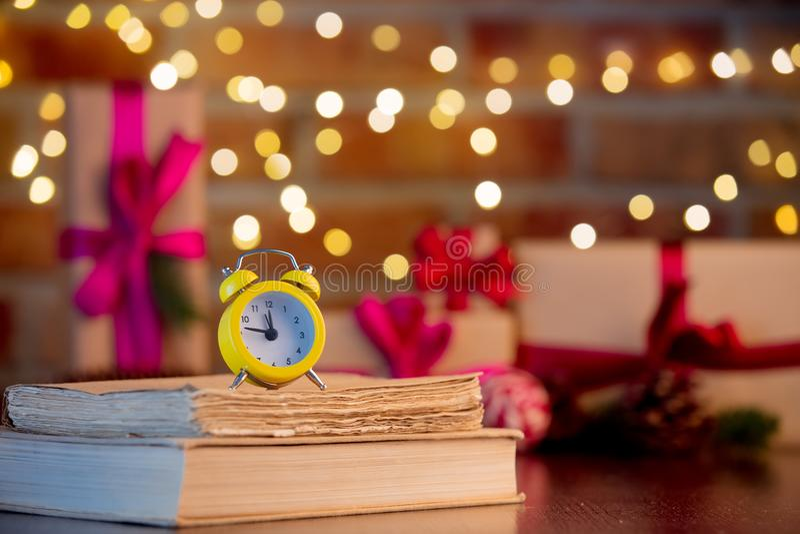 Wecker und Bücher auf Hintergrund mit feenhaften Lichtern lizenzfreie stockbilder
