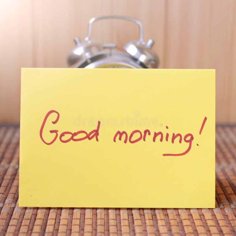 Wecker und ein Blatt Papier, das guten Morgen sagt stockfotos