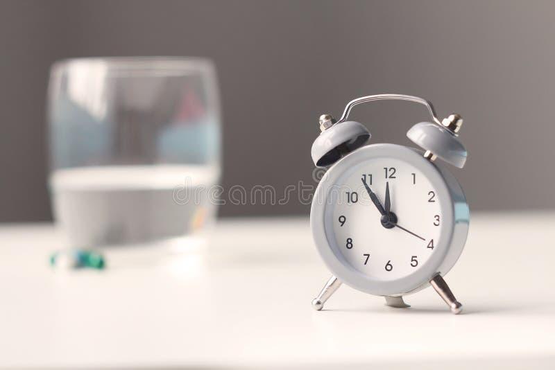 Wecker und medizinische Pillen auf Nachttisch Gesundheitspflege und Medizin lizenzfreie stockbilder
