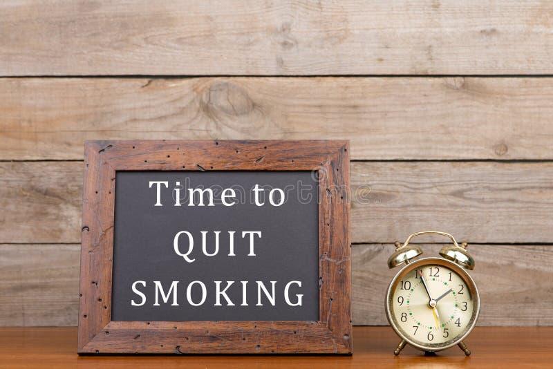 Wecker und Tafel mit Text u. x22; Zeit, smoking& x22 zu verlassen; lizenzfreie stockbilder