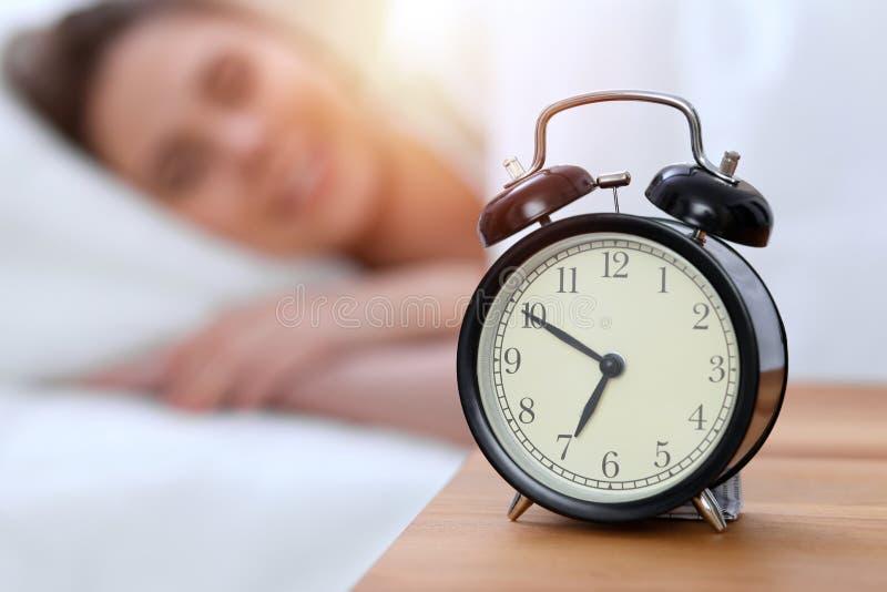 Weckergegenteil der schönen jungen schlafenden Frau beim im Bett bequem und himmlisch liegen Glückliches Aufwachen lizenzfreie stockbilder