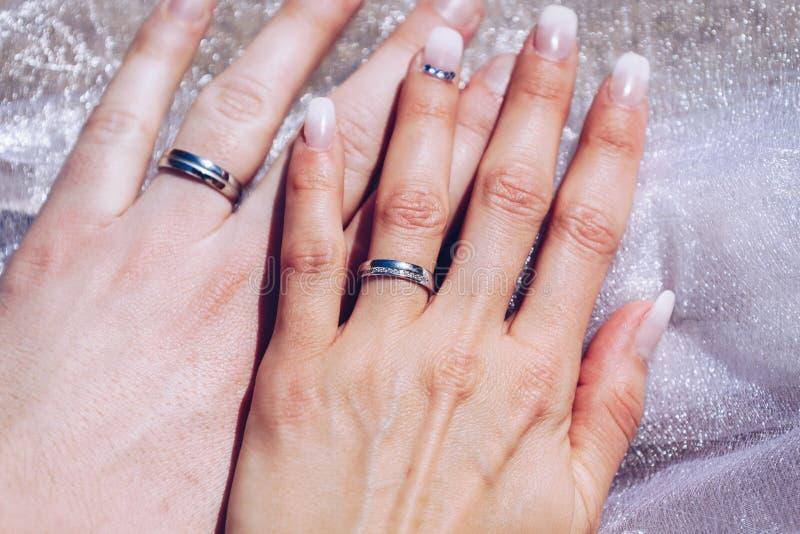 Wed recentemente as mãos do ` s dos pares com alianças de casamento imagem de stock
