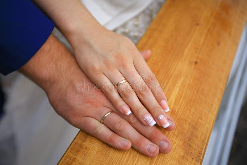 Wed recentemente as mãos do ` s dos pares com alianças de casamento Noiva e noivo fotografia de stock