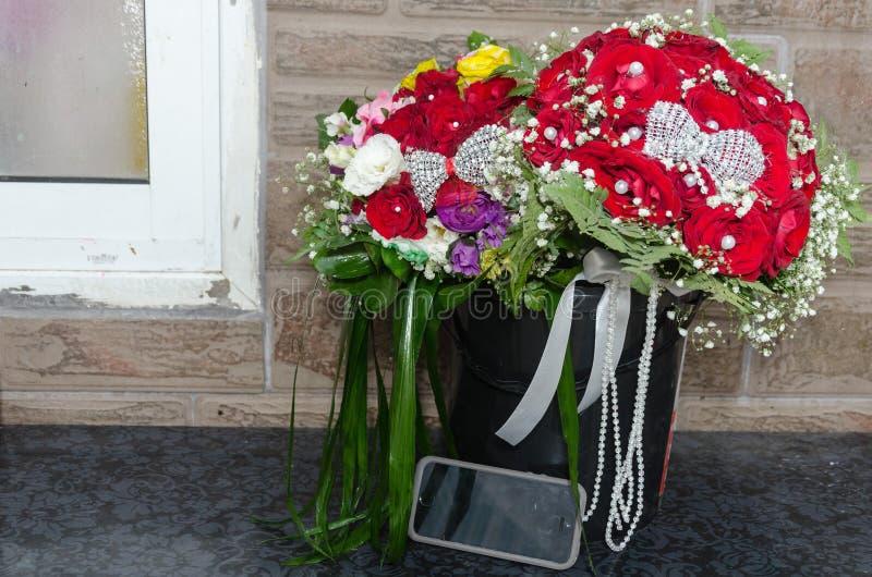 Wedding букет 2 красных роз и других красочных цветков и мобильного телефона стоковое изображение rf