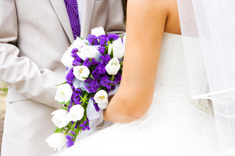 Wedding. Young couple in wedding wear with bouquet of flowers