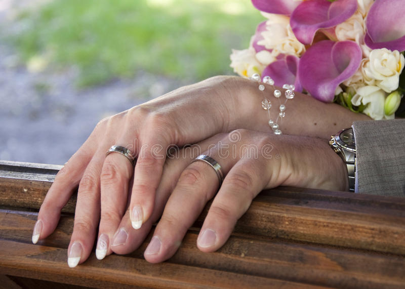 Wedding. Close-up bride and groom hands with wedding rings and a pink and white wedding bouquet stock photography