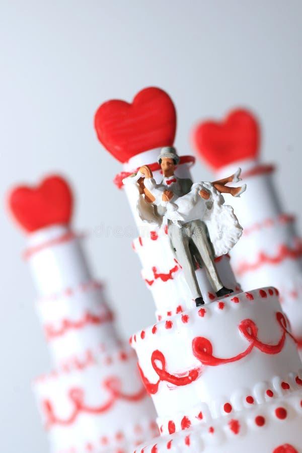 Wedding. Close up of mini figurine, groom carries bride on wedding cake royalty free stock photography