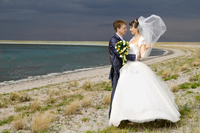 Wedding. The beauty happy married couple stand on coast, puff wind, imminent storm-cloud royalty free stock photography