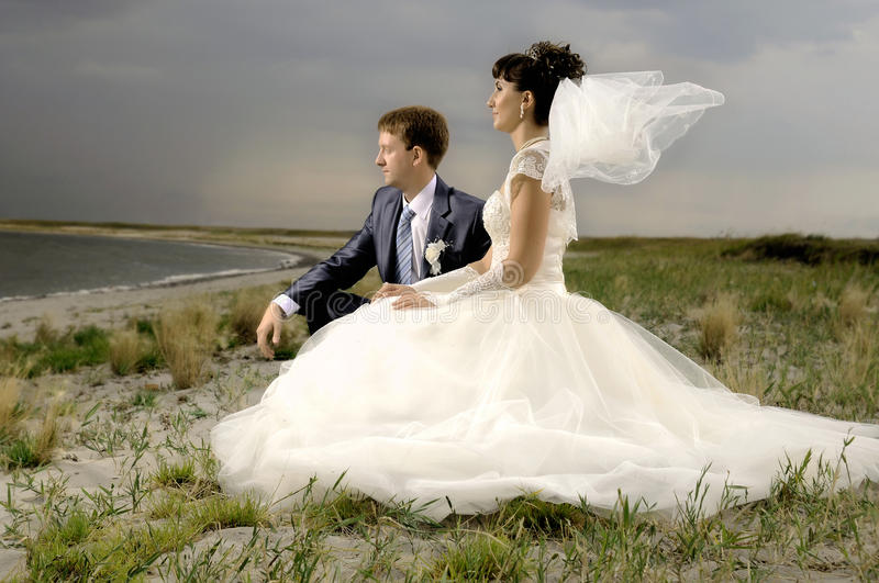 Wedding. The beauty happy married couple sit on coast, puff wind, imminent storm-cloud royalty free stock photos