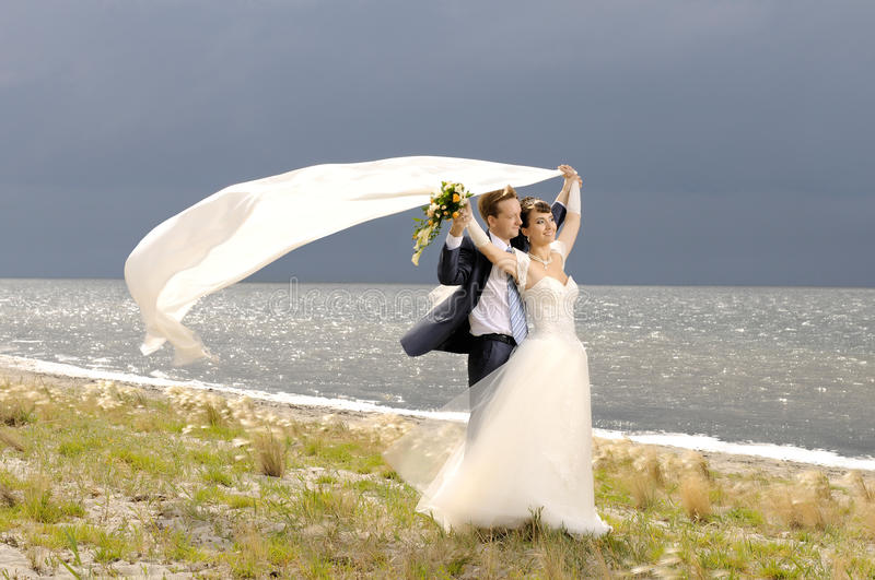 Wedding. The beauty happy married couple stand on coast, puff wind, imminent storm-cloud royalty free stock photos