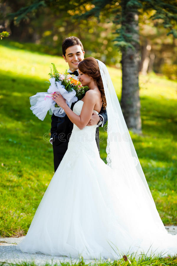 Wedding. Happy bride and groom at a park on their wedding day stock image