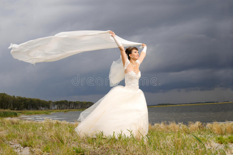Wedding. The beauty happy married couple stand on coast, puff wind, imminent storm-cloud stock photo