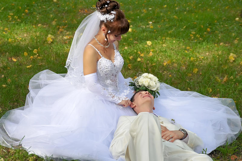 Wedding. Couple of young men cuddling on the grass during the holiday walk royalty free stock images