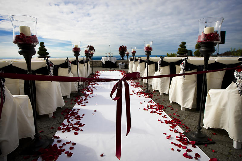 Wedding. A beautiful outdoor wedding setup with red ribbon under a cloudy blue sky royalty free stock images