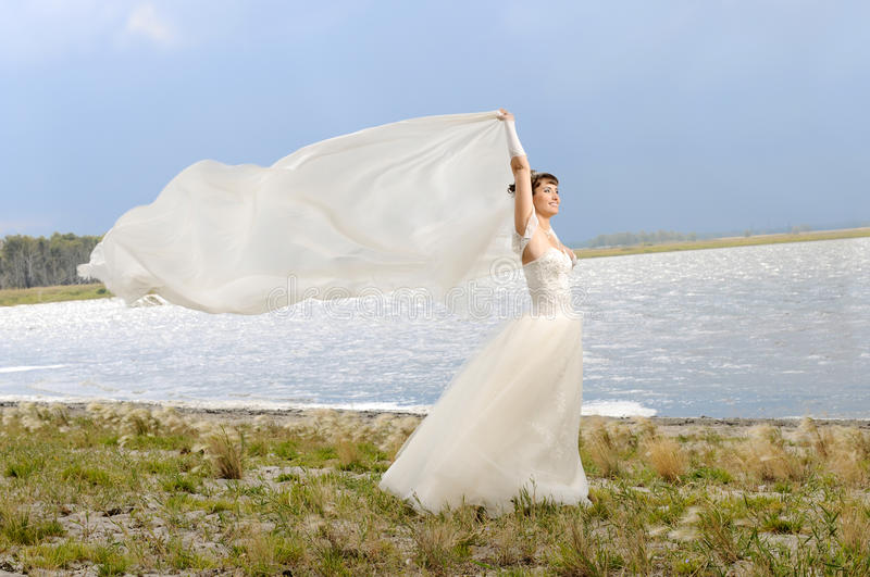 Wedding. The beauty happy married couple stand on coast, puff wind, imminent storm-cloud stock photography