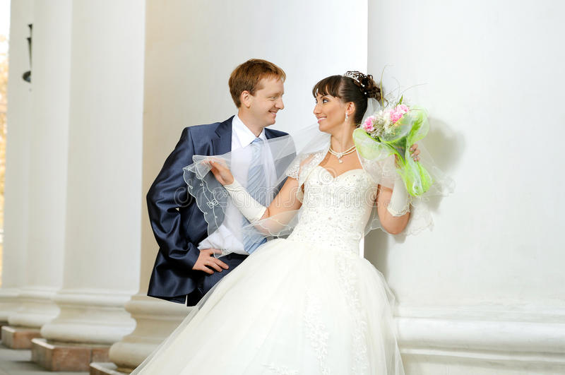 Wedding. The cutie happy married couple bride on architecture background, horizontal photo royalty free stock image