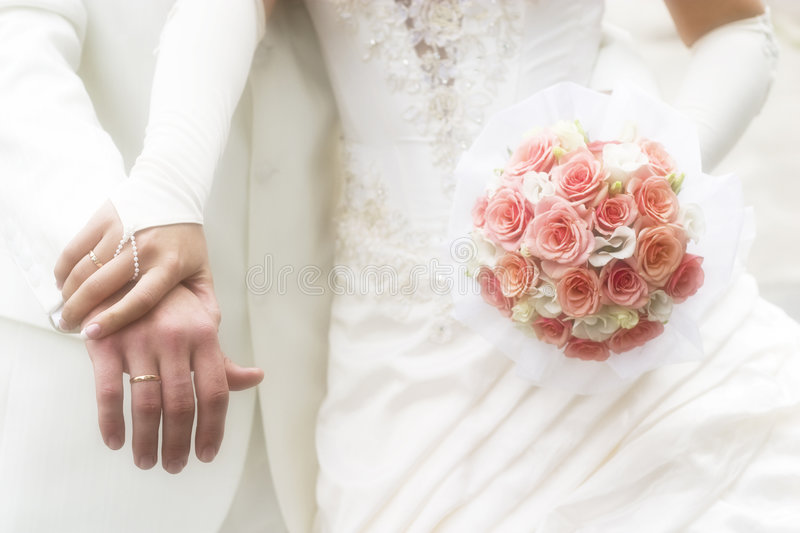 Wedding. Just married - young couple in wedding wear with bouquet of roses. Soft-focused image in high key royalty free stock photography