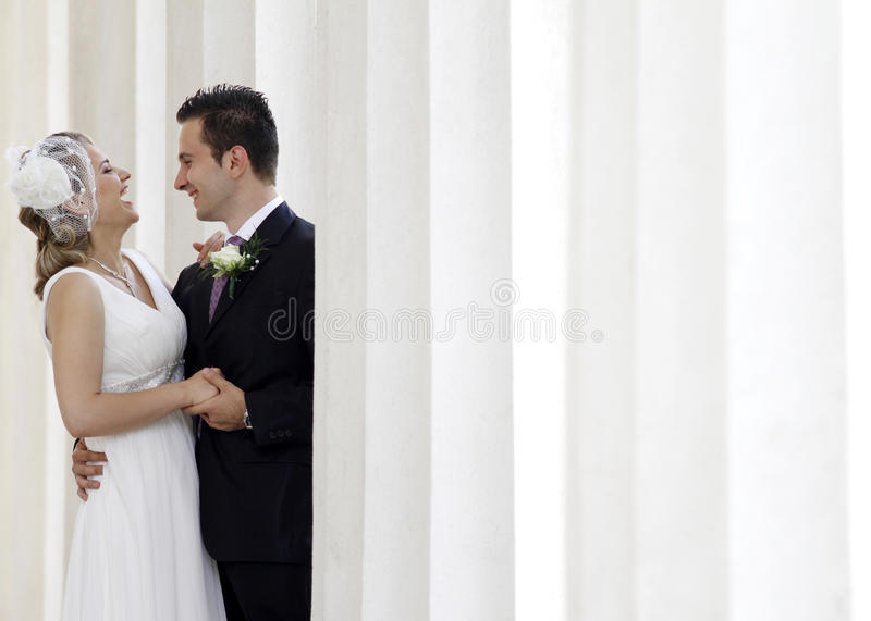 Wedding. Happy wedding couple laughing between white columns