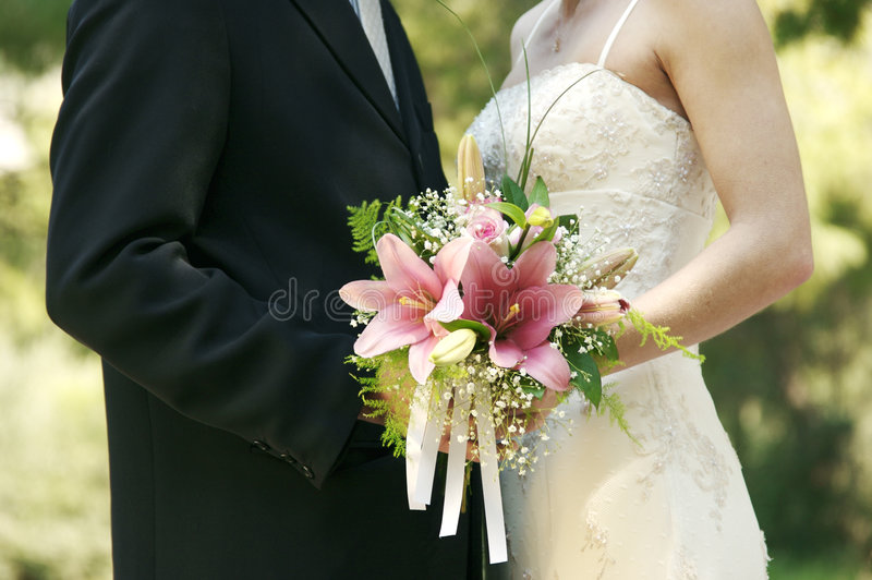 Wedding. Newly-wed couple holding wedding bouquet royalty free stock images