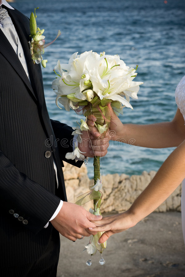 Wedding. Bride and groom holding the wedding bouquet stock photo