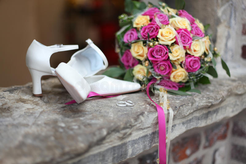 Wedding accessoires. Like rings, shoes, flowers and bouquet defocused royalty free stock image