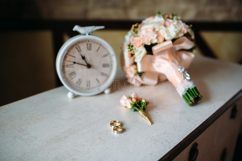 Wedding accessories. Boutonniere, Golden rings, a beautiful bouquet of flowers on white textured table. Concept of bride. And groom ornamentation stock image