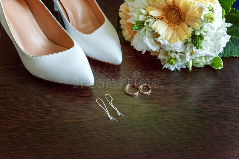 Wedding accessories close up. Wedding accessories. bridal shoes, bouquet, earrings and rings on wooden background royalty free stock photo
