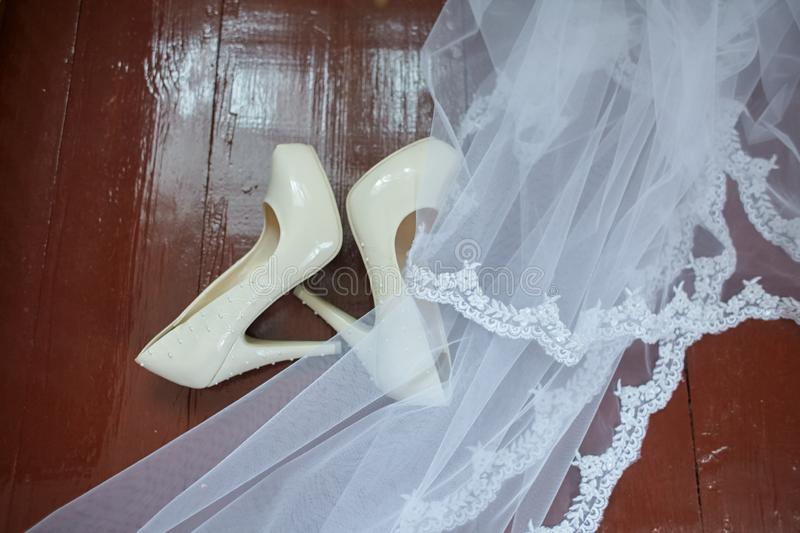 Wedding accessories. Bridal shoes  and veil on the wooden floor at wedding morning preparation stock photo