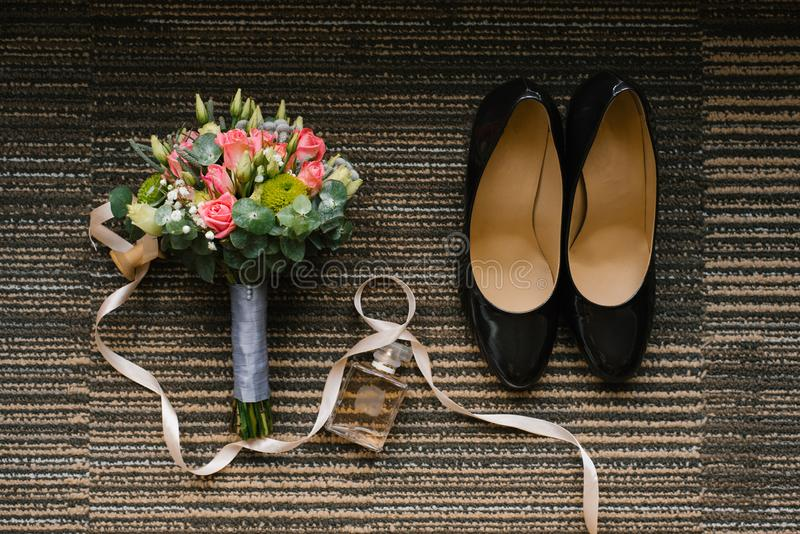 Wedding accessories of the bride: shoes, bouquet of roses and eucalyptus royalty free stock image