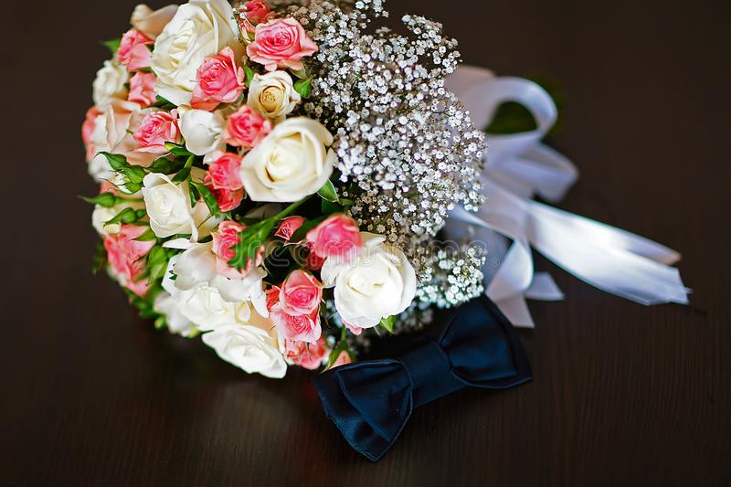 Wedding accessories of the groom, dark blue butterfly with a flower bouquet stock photography