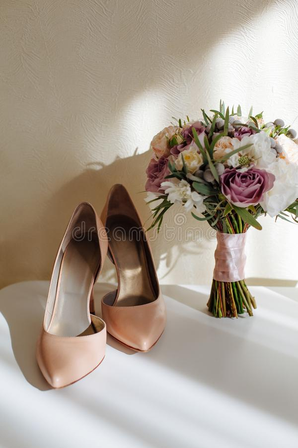 Wedding accessories for the morning of the bride. Wedding bouquet and shoes of the bride. Wedding accessories for the morning of the bride. Wedding bouquet and stock photos