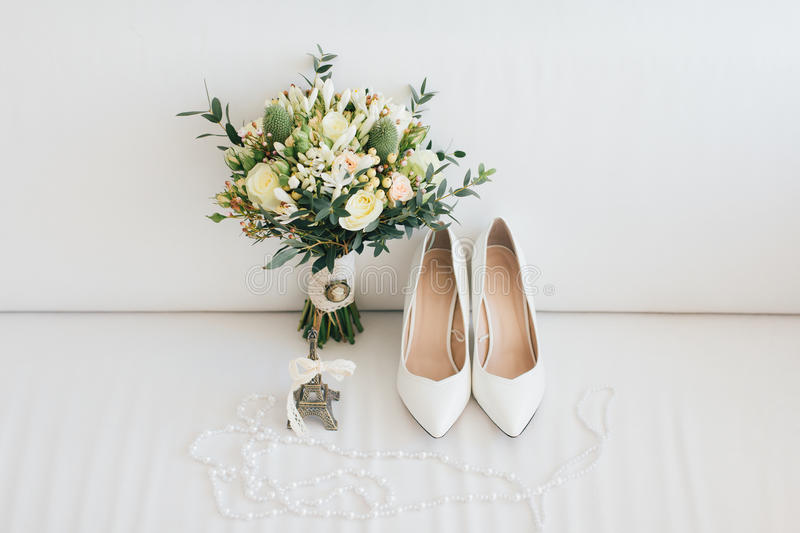 Wedding accessories. Shoes and bouquet of the bride stock photos