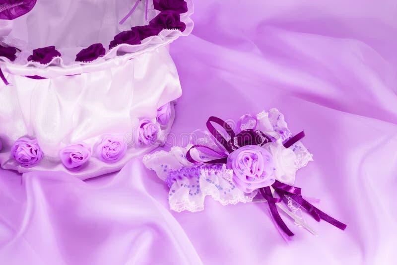 Wedding accessories in ultraviolet. Wedding accessories on silk canvas in ultraviolet light stock photo