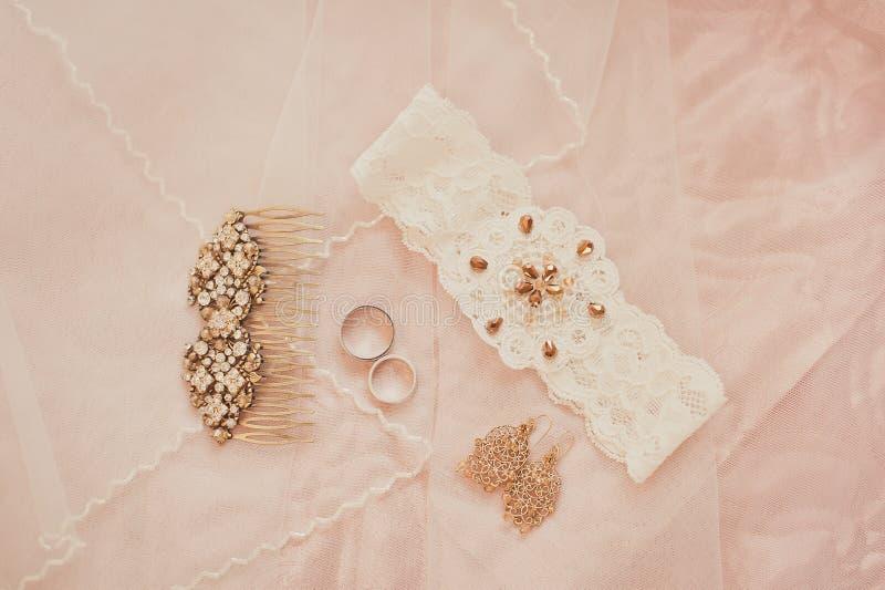 Wedding accessories, wedding rings. Wedding gold vintage earrings, wedding garter for the bride stock image