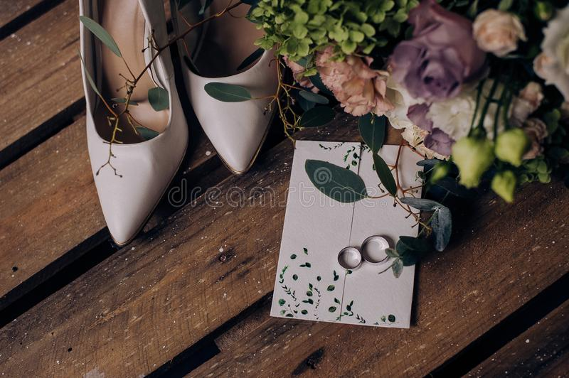 Wedding accessory bride. Stylish beige shoes, earrings, gold rings, flowers, garter on wooden background royalty free stock image