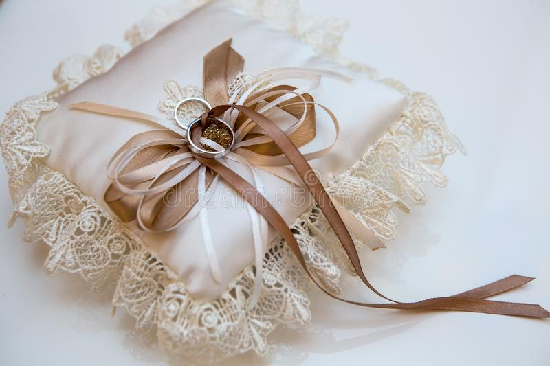 Wedding accessory, embroidered lace pillow with rings of the bride and groom, still life in cream royalty free stock image