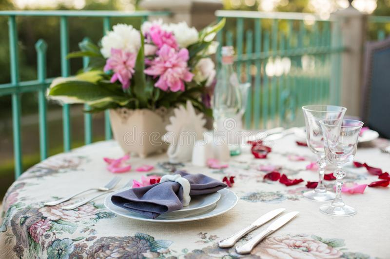 Romantic decor of the festive table in the restaurant with candles, flowers, rose petals stock photography