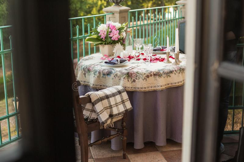 Romantic decor of the festive table in the restaurant with candles, flowers, rose petals royalty free stock photo