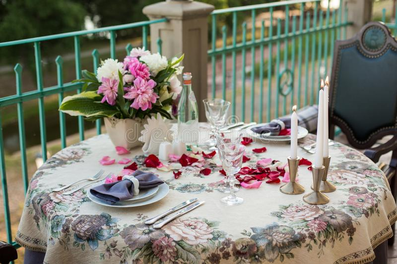 Romantic decor of the festive table in the restaurant with candles, flowers, rose petals royalty free stock photos